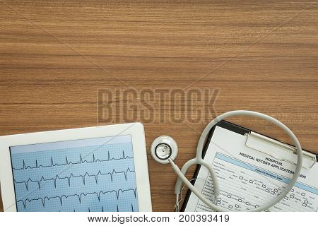 Cardiograph Ekg Electrocardiogram Heart Showing In Tablet Computer And Medical Documents On Desk Of