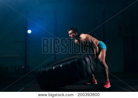 Full length picture of confident young man with naked torso exersicing with tire. Weightlifting or functional training. Sports and fitness concept.