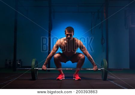 Weightlifting or functional training. Muscular man with naked torso working out in gym with barbell. Sports and fitness concept.