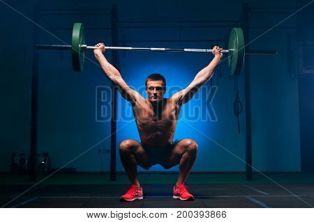 Strong muscular man with naked torso working out with weight in gym. Fitness man lifting barbell. Weightlifting or functional training. Sports and fitness concept.