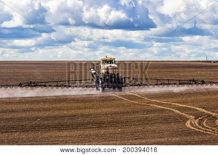 tractor spraying a field on farm fertilizes the land