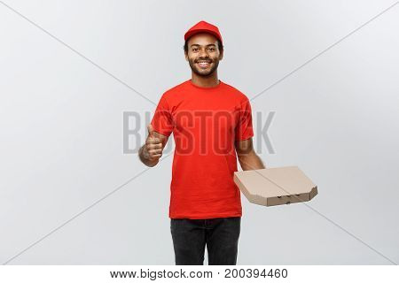 Delivery Concept - Portrait of Happy African American delivery man holding a pizza box package and showing thumps up. Isolated on Grey studio Background. Copy Space.