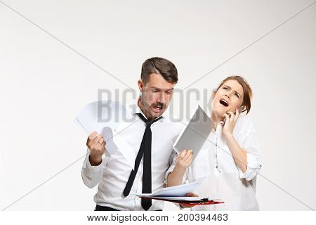 The surprised emotional business man and woman communicating on a gray studio background
