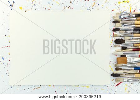 Various Paintbrushes And Blank Paper Sheet On Background With Watercolor Blobs