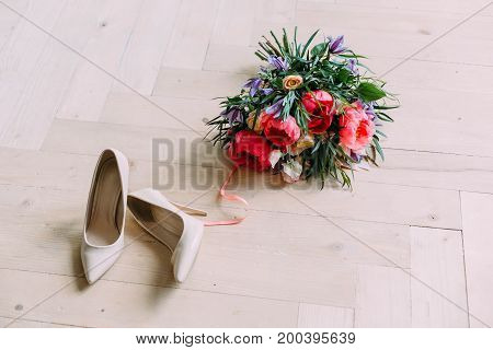 Rustic wedding bouquet with white roses crimson peonies and shoes on a wooden floor. Close-up. Indoors.