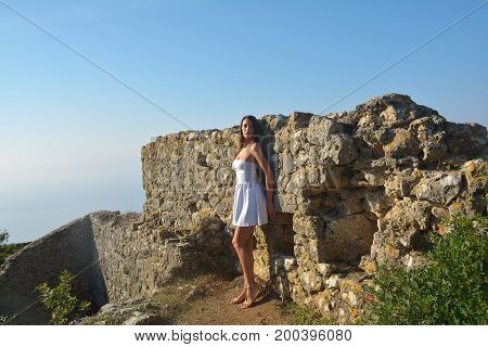 Attractive girl on old ruins in summer