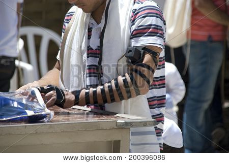 Jerusalem, Israel - May 07, 2012: Orthodox jews with black straps Tefillin on square in front of the Western Wall in Jerusalem, in May 2012
