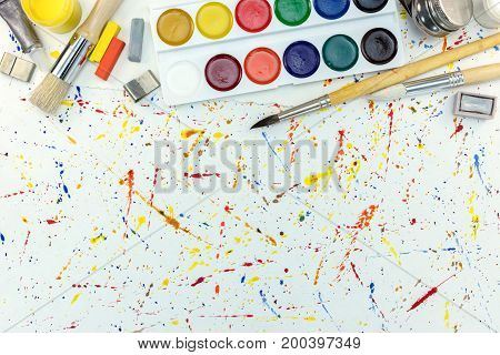 Artistic Paintbrushes And Watercolor Paints With Pastel Chalks Top View