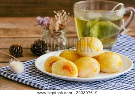 Chinese pastry with sweet mung bean and salted egg. Moon cake or Chinese pastry filled with mung bean paste and salted egg served with green tea. Delicious homemade Chinese pastry ready to served. Chinese pastry on white plate.