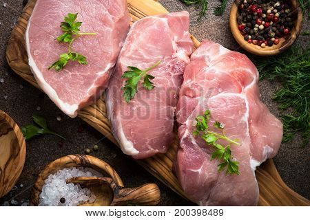 Fresh meat. Raw pork steak on a cutting board with herbs and spices.