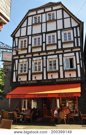 Hattingen, Germany - August 15, 2012: Exterior view of a traditional half-timbered house called Fachwerkhaus in Germany, hosting a small bakery store, where people enjoy their coffee, in August 2012.