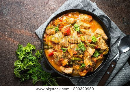 Stewed pork with vegetables in tomato sauce in a cast-iron pan on dark stone table. Top view copy space.