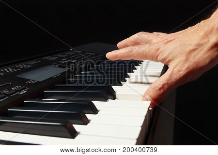 Hand of pianist playing the electronic synthesizer on a black background
