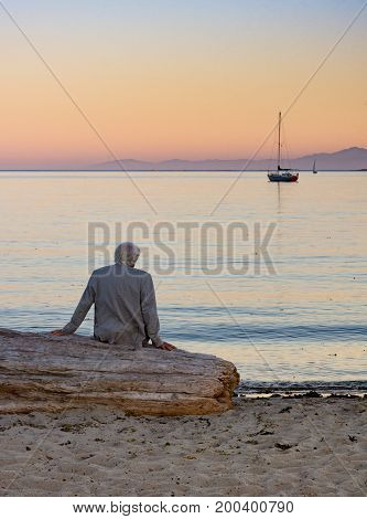 A gray haired man in a beige jacket with his back to the camera seated on driftwood looking at the sailboats on the ocean at sunset.