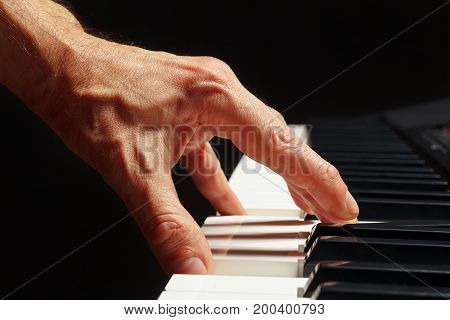 Hand of pianist play the keys of the electronic synth on a black background close up