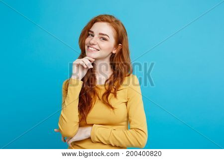 Lifestyle concept - Close up Portrait young beautiful attractive ginger red hair girl playing with her hair with shyness. Blue Pastel Background. Copy space.