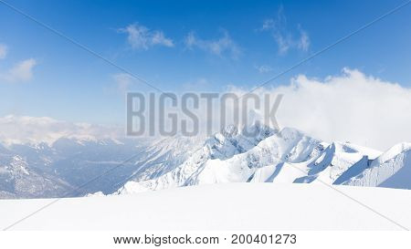 High mountains lots of white pure snow and clouds lie on the mountains in Sochi Russia