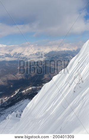 High mountains lots of white and pure snow and clouds lie on the mountains in Sochi Russia