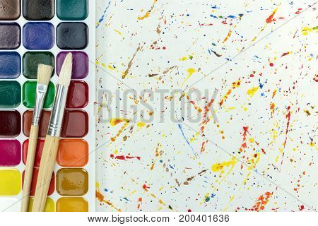 Watercolor Paints And Paintbrushes On Aquarelle Splashes On White Paper Background