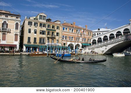Venice, Italy - October 2013: Gondola near Rialto Bridge in Venice in October 2013, with people onboard and walking along the Canal