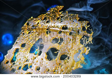 Macro detail of cannabis oil concentrate aka shatter against dark background with smoke