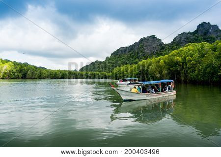 Langkawi, Malaysia - 2nd May 2017: Tourists wait on a boat on a lagoon to see the eagle feeding. Eagles are the mascot of Langkawi and the Kilim river cruise is a great way to see them