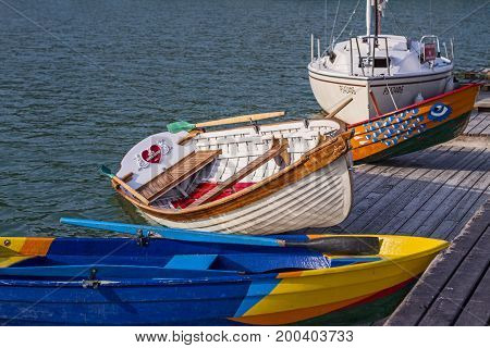 Colored wooden painted bright boats and a yacht in the water of the black sea near the deck swing on the waves.