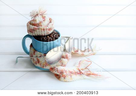 Blue mug filled grains of black coffee warm scarf hat and sunglasses / winter holiday concept