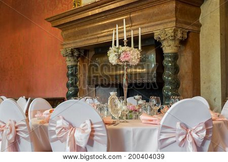 Candles burning in a chandelier on elegant dinner table.