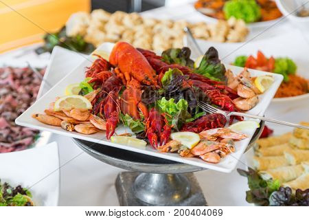 Cooked cancer at a banquet table for a wedding. Snack for beer. Big plate of tasty boiled crawfish closeup on wooden table, seafood dinner, nobody