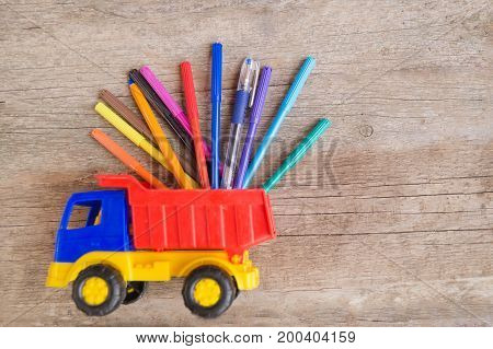 Colorful felt-tip pens and ball pens in the toy truck on the wooden table. Space for text