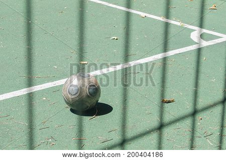 Soccer ball on a green artificial turf football field. View behind the lattice.