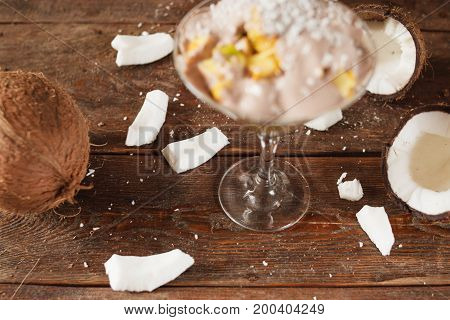 Demonstration of culinary art of fresh fruit salad in martini glass with coconut flakes. Sweet dessert with decoration on wooden background