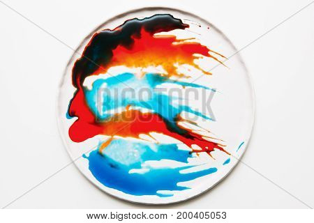 Abstract image of colorful spatters on white round plate. Watercolor blots of bright orange, red, deep brown and turquois colors flowing each other on surface