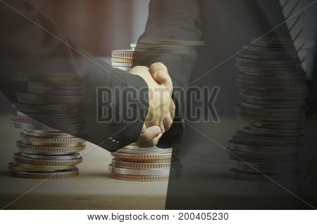 double exposure businessman shaking hand and money coins concept in corporate and communicate to success and negotiate in finance