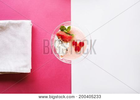 Creamy strawberry dessert on contrast crimson and white background. Sweet fruit souffle decorated with fresh red berry and mint, top view with free space