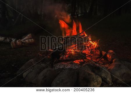 large campfire, bonfire outdoors with burning coals and flames.