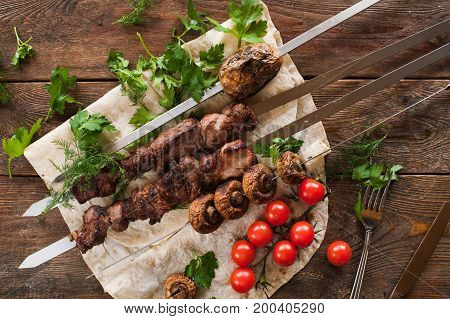 Shish-kebab with field mushrooms and cherry tomatoes on lavash. Barbecue, natural food preparing on fresh air, top view