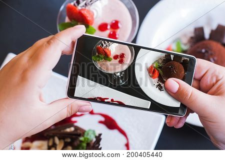 Food photos of delicious desserts by smartphone in restaurant. Creamy strawberry souffle and chocolate fondant, photo shooting and new technology, close up pov picture
