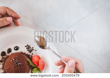 Tasting of delicious chocolate dessert for real gourmet. Customer eats fondant with decoration from strawberry and mint in restaurant, close up picture with free space