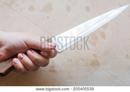 Woman holds knife in hands on cutting board background. Beginning of cooking process in kitchen, empty desk, top view picture with free space