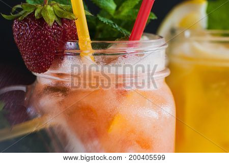 Close up just preparing fresh fruit cocktails in glass jar. Strawberry and orange cold drink with mint and ice, refreshment in hot weather, focus on foreground