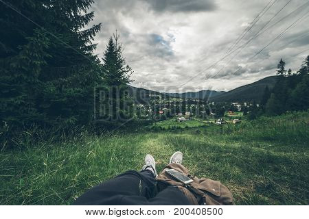 man lying on the ground and enjoying view of summer mountains