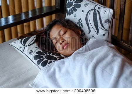 Young Asian woman sleeping peacefully in the bacony during summer vacation