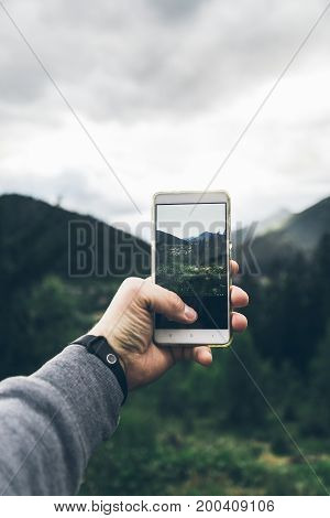 man taking picture of the mountains on his phone in cloudy weather