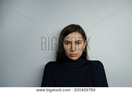 Nonverbal communication. Headshot of beautiful young Caucasian female frowning staring at camera with suspicious distrustful look narrowing her eyes. Suspicion distrust and doubt concept