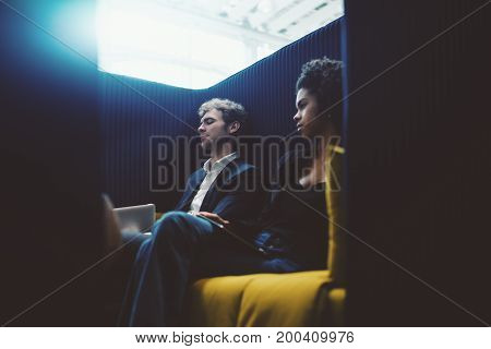 View through door aperture of black young businesswoman and caucasian man entrepreneur sitting both on greenish sofa in chill out recreational area of modern office and having rest