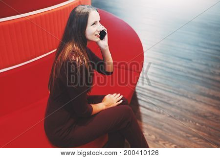 Smiling attractive caucasian woman with long golden hair is sitting on red round sofa and having phone conversation with her husband with copy space place for message your advertising or logo