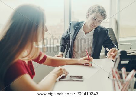 Two business persons (woman in red dress and caucasian handsome man in formal suit) having work meeting in bright office room; woman is explaining something to colleague with drawing on paper sheet