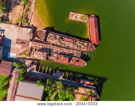 Aerial view, two old, rusty barges, moored at the pier on river, summer, green water.